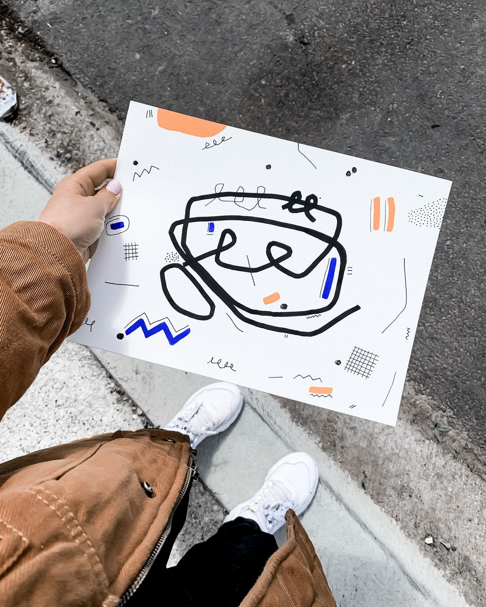 person holding white printer paper with drawing