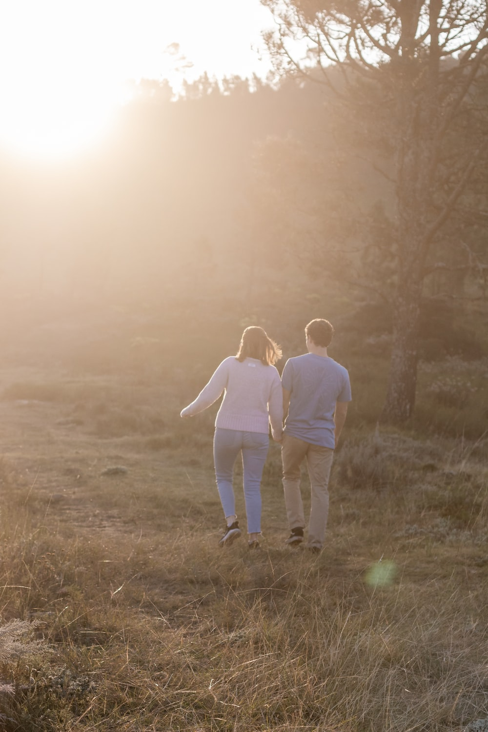 man and woman walking on grass field during daytime