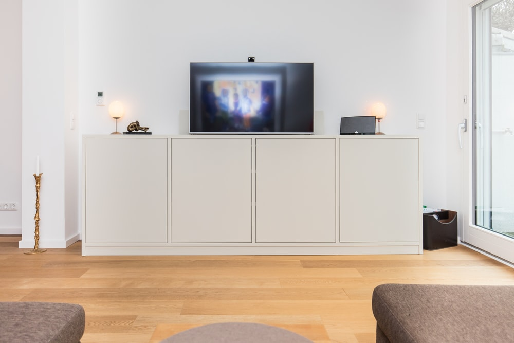 black flat screen tv turned on on white wooden tv hutch