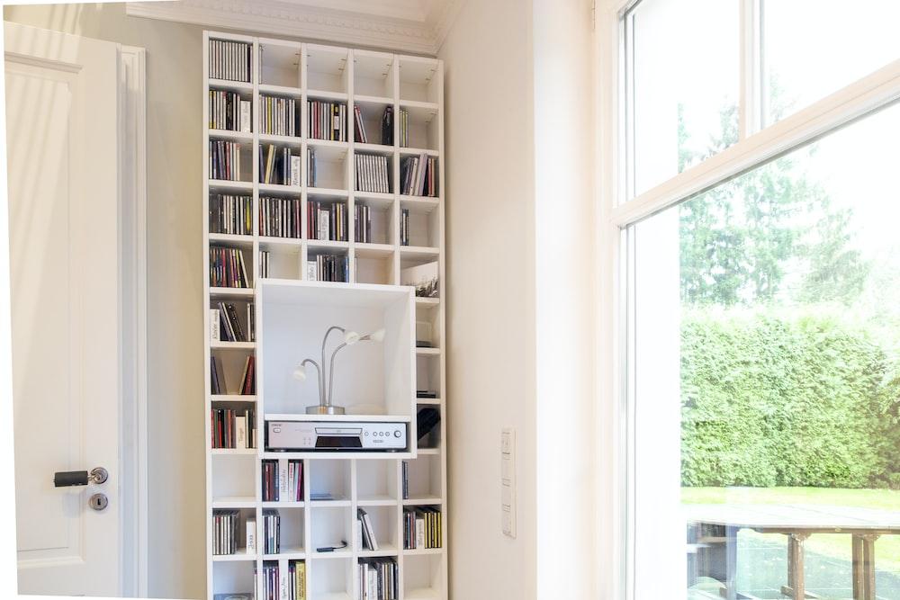 white wooden book shelf near window