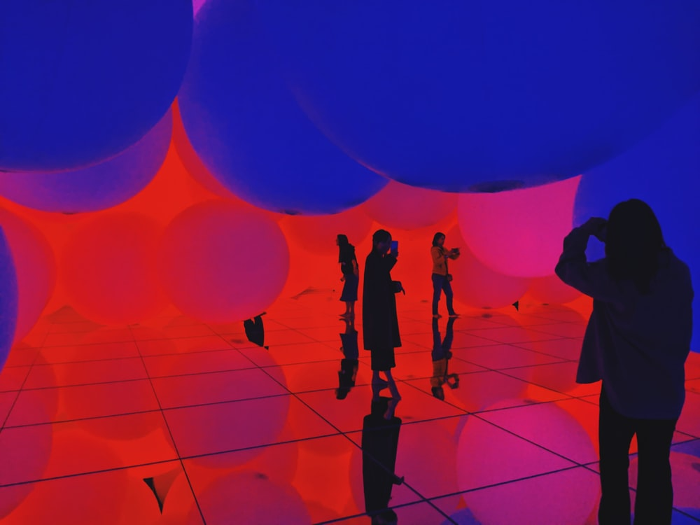 silhouette of people standing on blue and red balloons