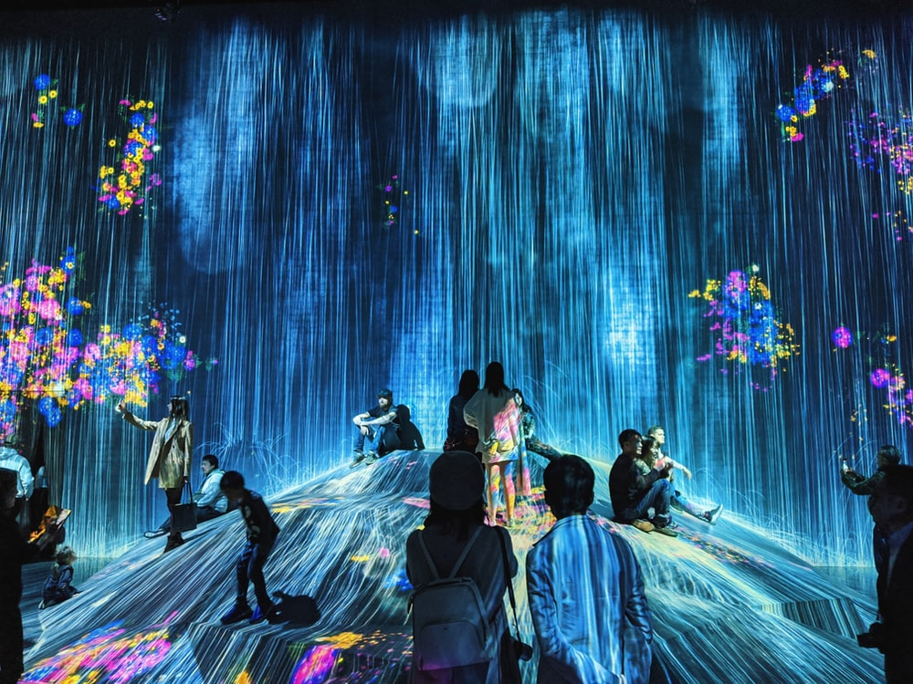people dancing on stage with blue lights