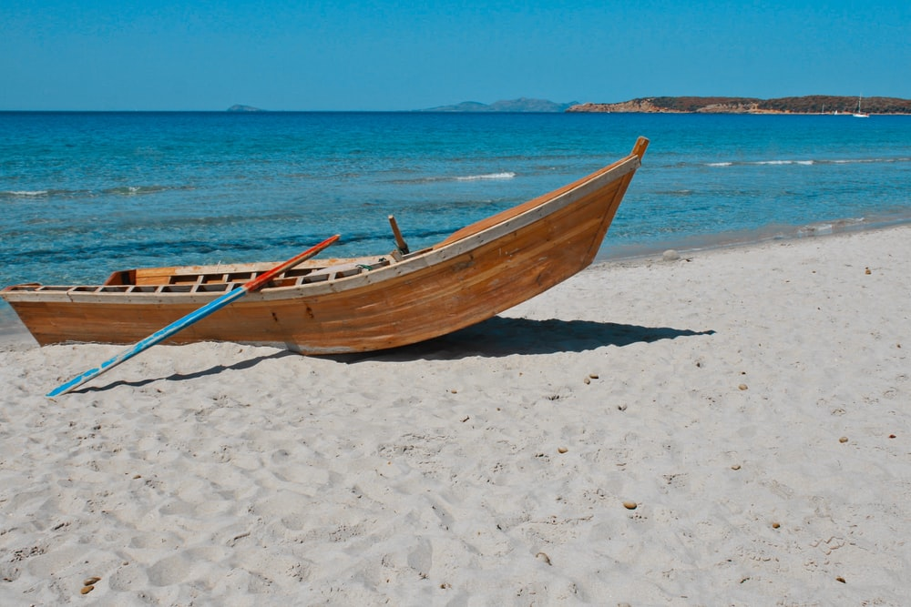 brown wooden boat on white sand beach during daytime