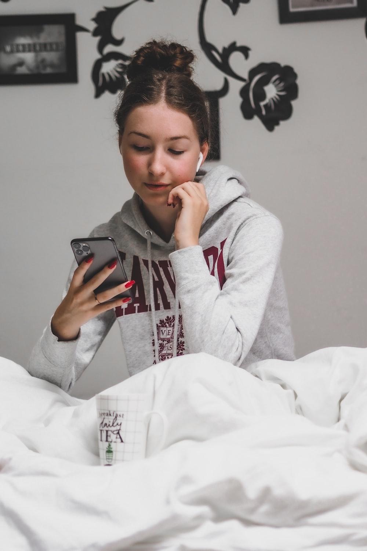 woman in gray hoodie holding black smartphone