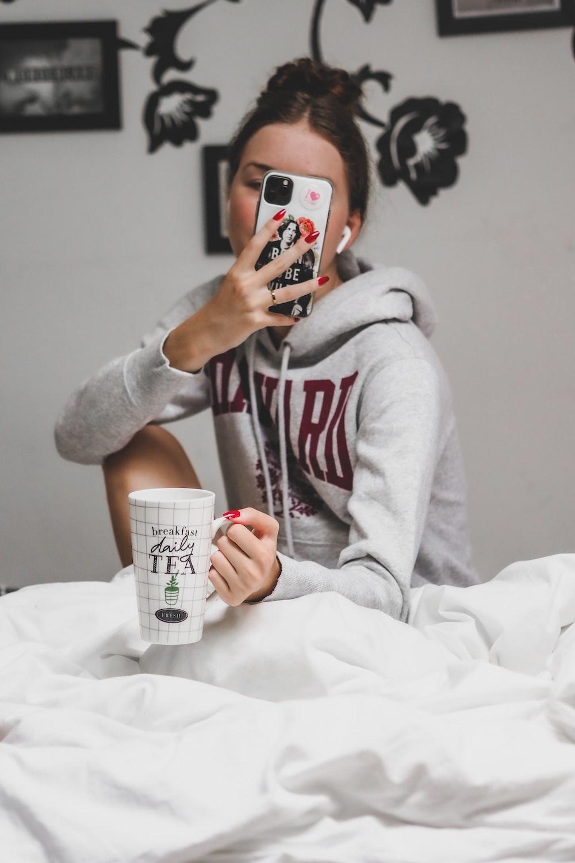 woman in gray hoodie holding white ceramic mug