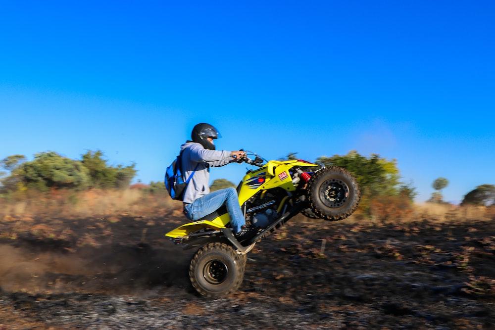 man in blue jacket riding yellow atv