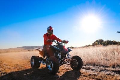 man riding atv on brown field during daytime suzuki zoom background
