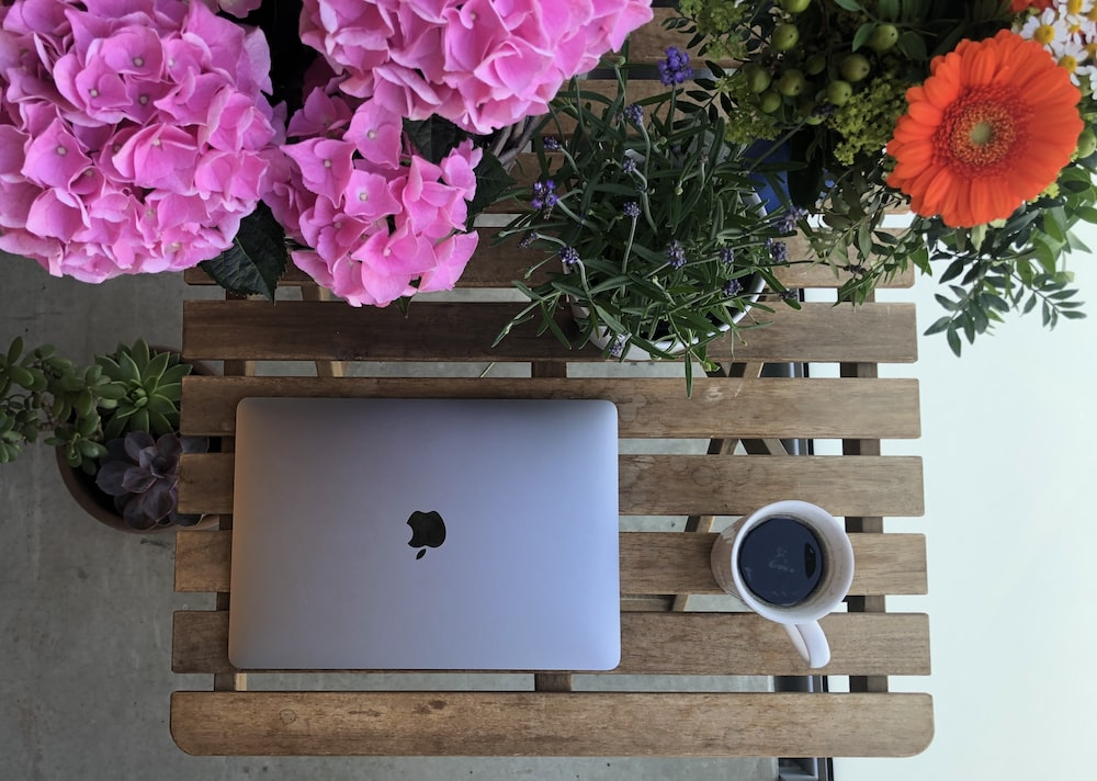 silver macbook beside white ceramic mug on brown wooden table