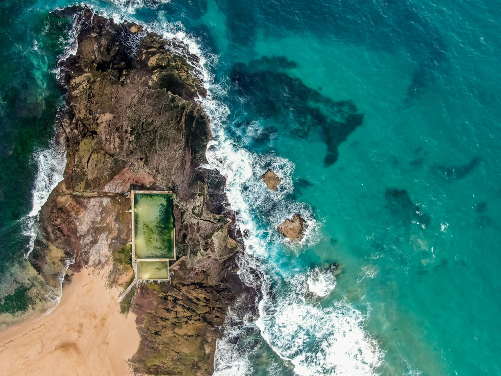 aerial view of green and brown house on brown rocky shore near body of water during