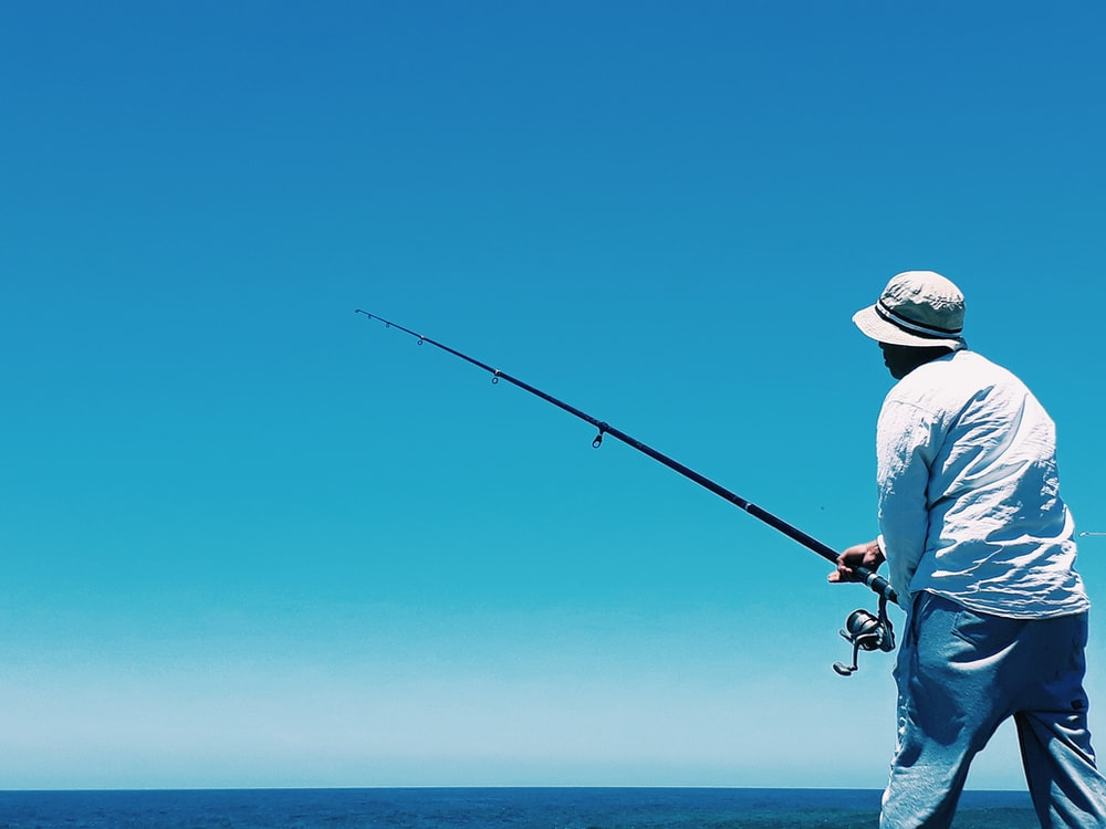 man in white shirt and blue denim jeans holding black fishing rod