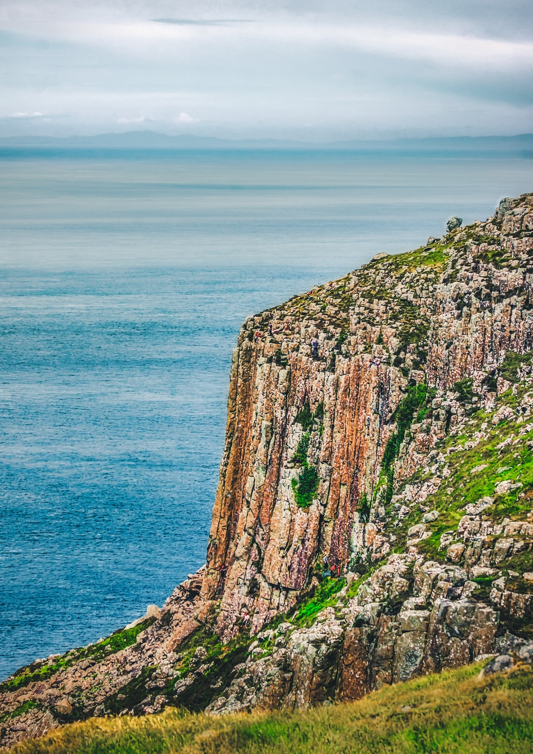 """The volcanically formed hexagonal rocks known as """"chimney stacks"""" on the face of Fair Head in County Antrim overlooking the North Atlantic. Rock climbers can be seen on the cliff face, and the coast of Scotland can be seen on the horizon (Jun., 2020)."""