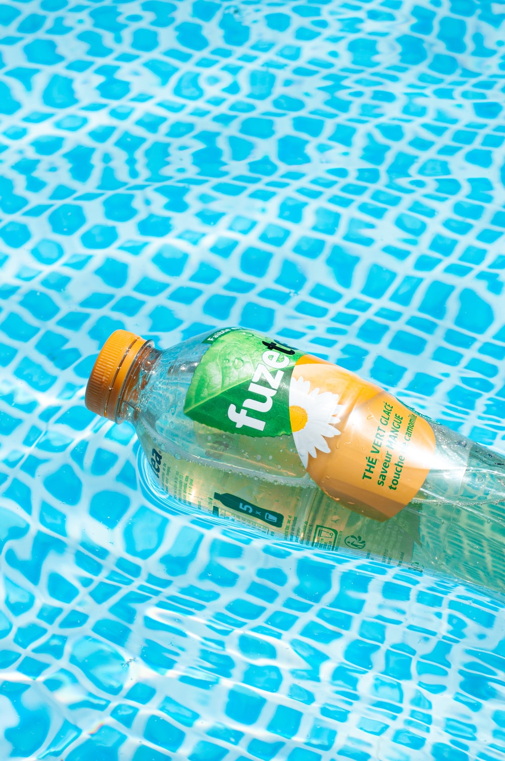 green labeled plastic bottle on blue and white polka dot textile