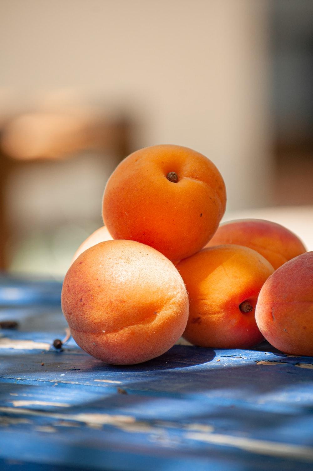three orange fruits on blue wooden table