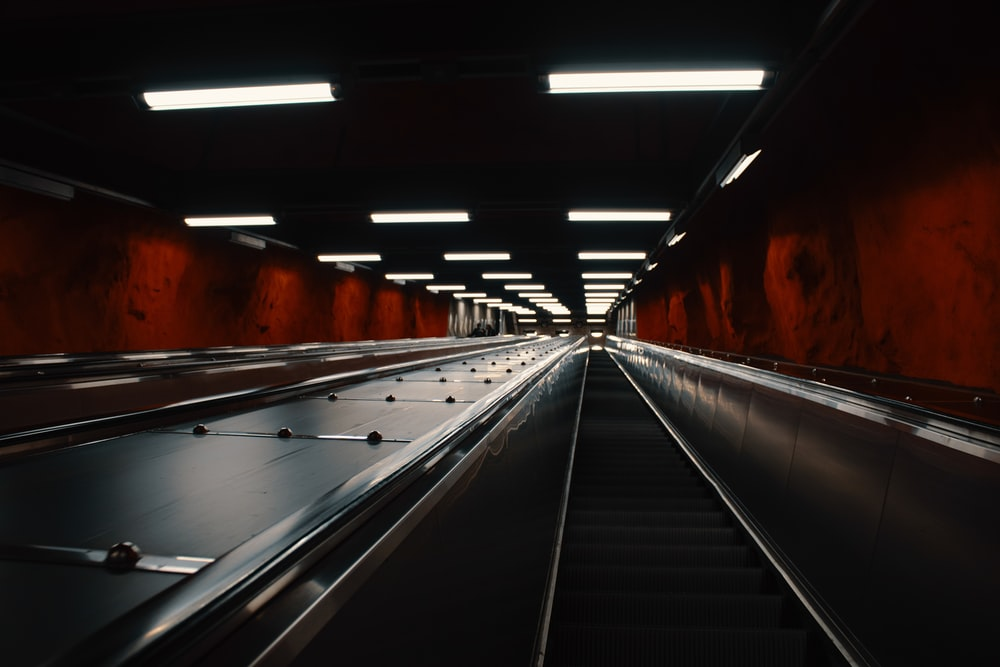 black and white escalator in tunnel