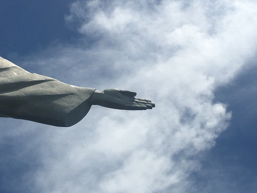 low angle photography of gray concrete statue under blue sky during daytime