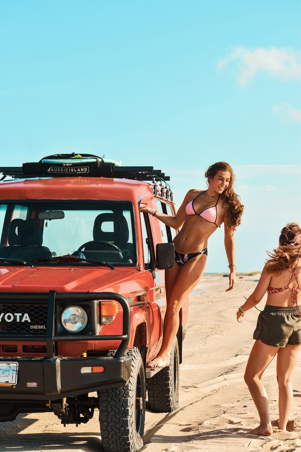 woman in black bikini standing beside red car during daytime