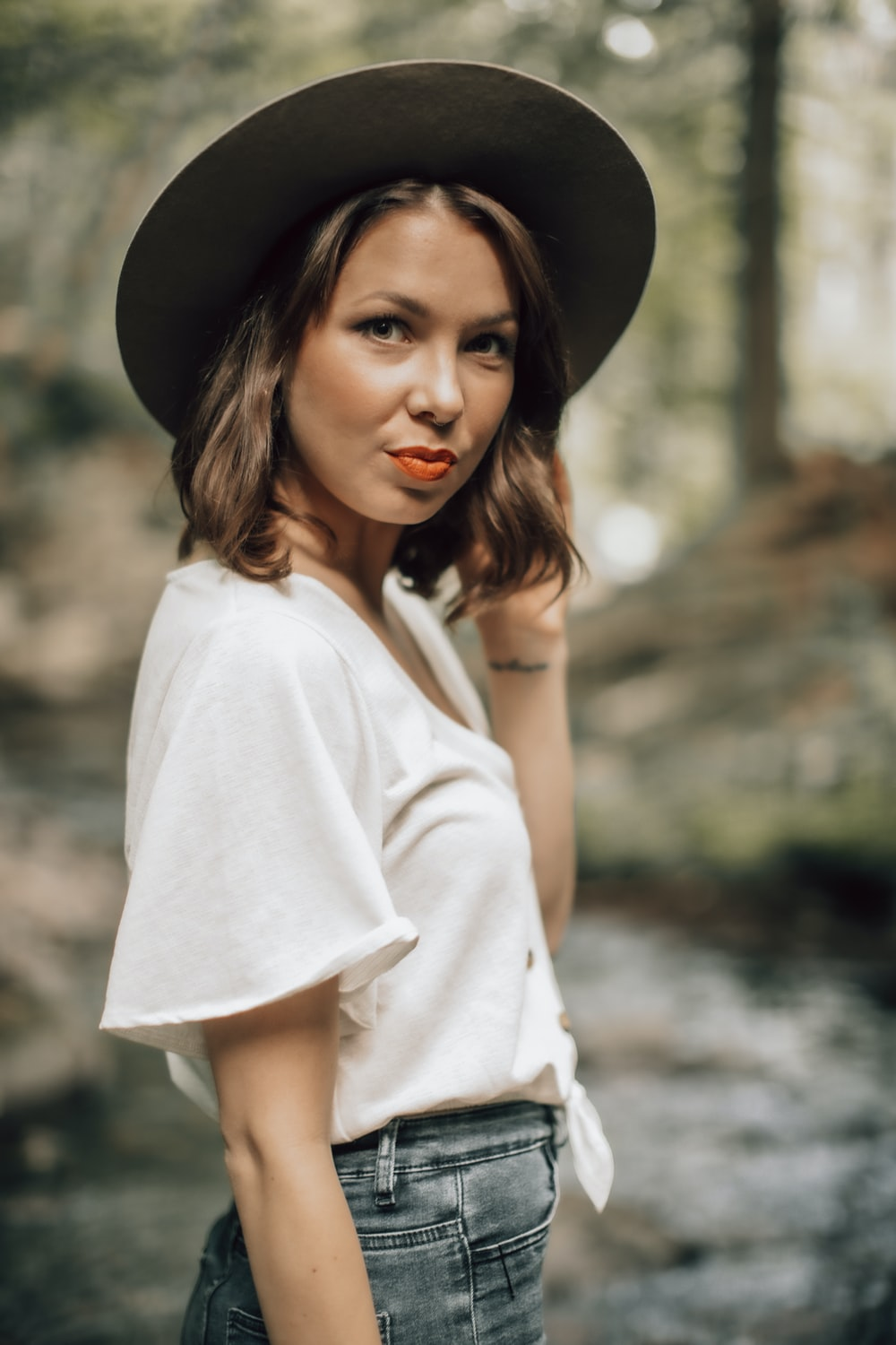 woman in white long sleeve shirt wearing black hat
