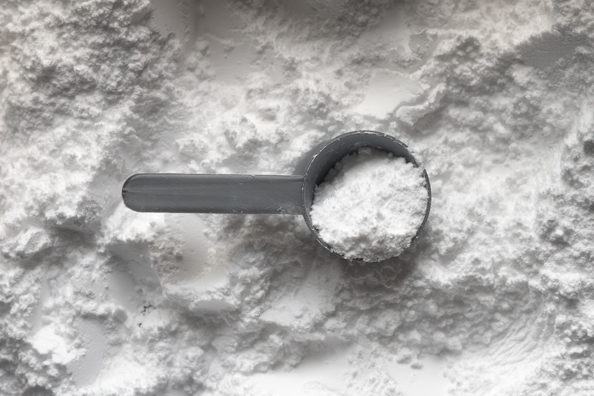 One scoop of white creatine monohydrate powder. A sports supplement that is well studied and researched within the health and fitness industry, it helps to increase strength, muscle mass and endurance.