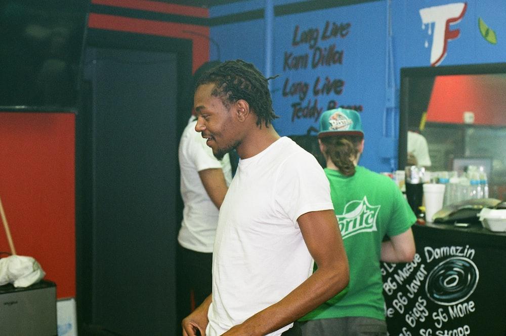 man in white crew neck t-shirt sitting beside man in green t-shirt