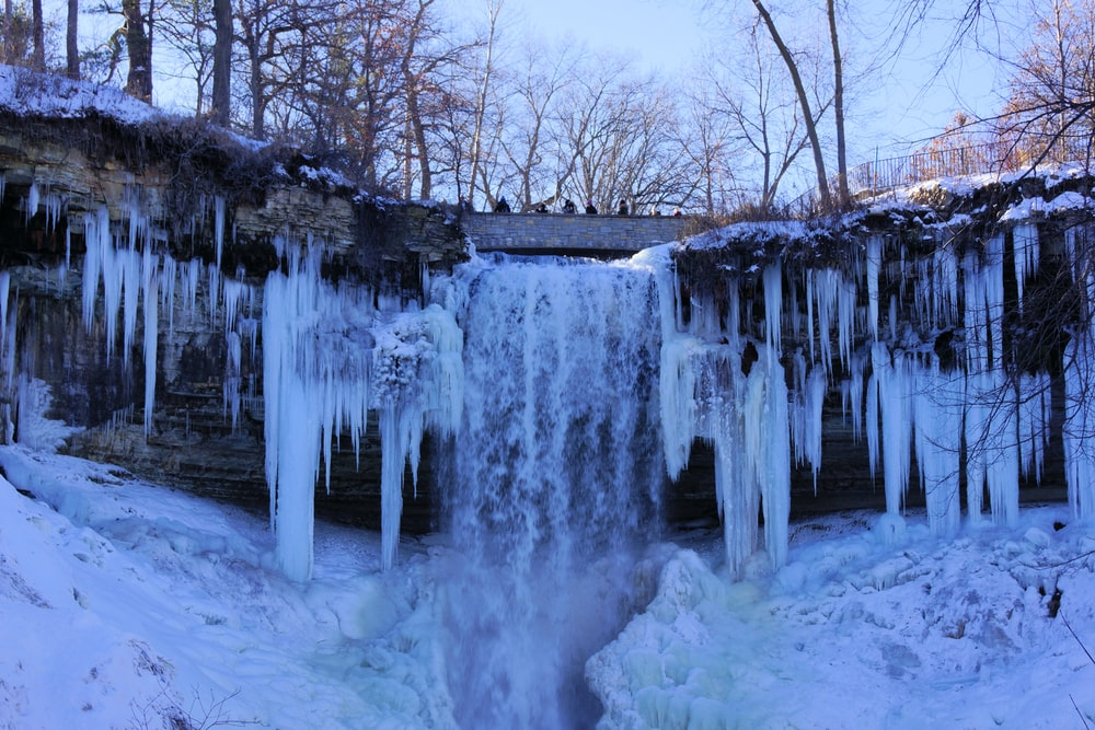 water falls in the middle of snow covered ground