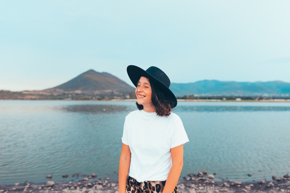 woman in white t-shirt and black hat standing on rocky shore during daytime