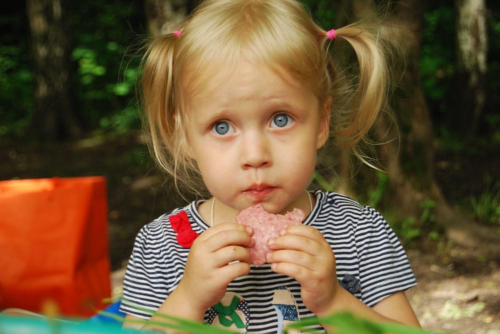 girl in blue and white stripe long sleeve shirt holding ice cream