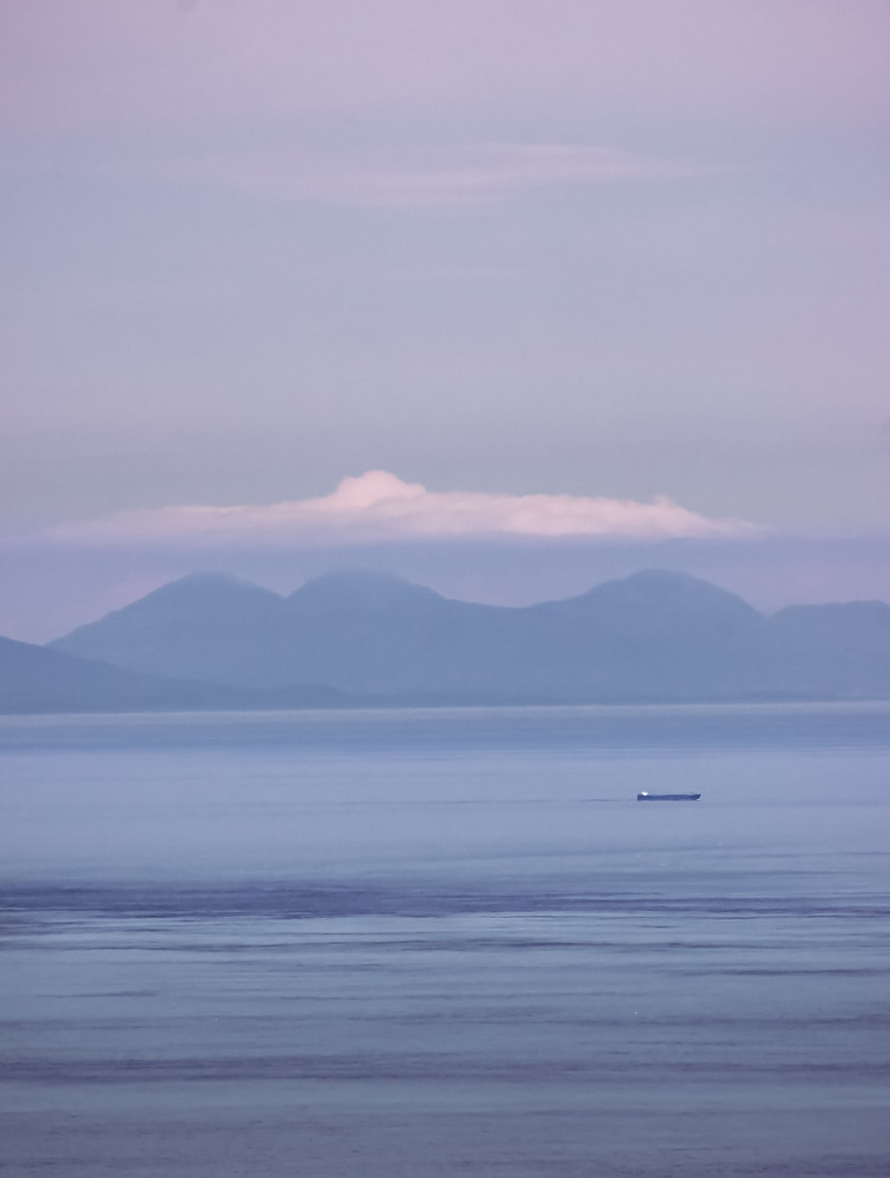 boat on sea near mountain during daytime