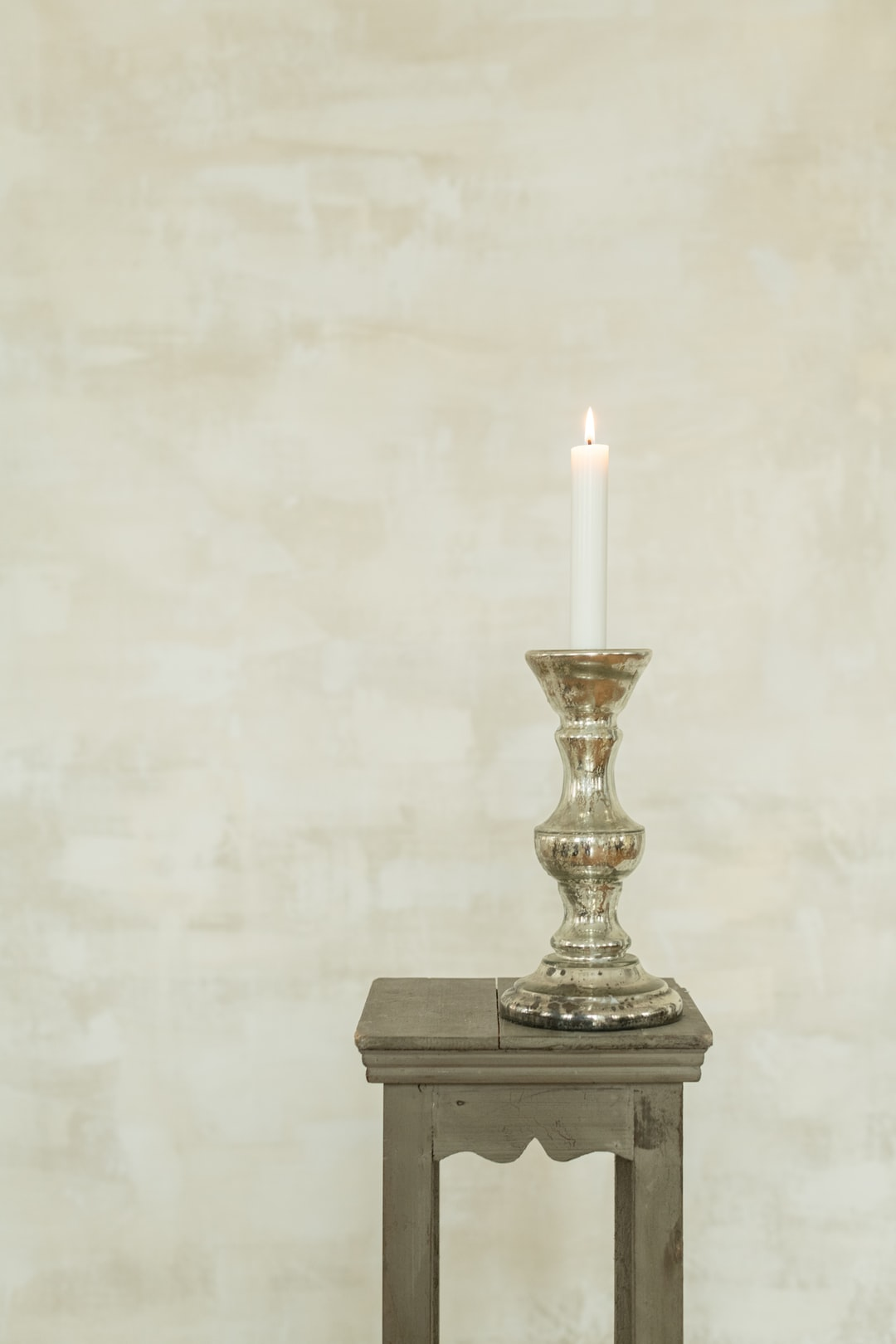 vintage glass candlestick with candle in front of a painted canvas backdrop