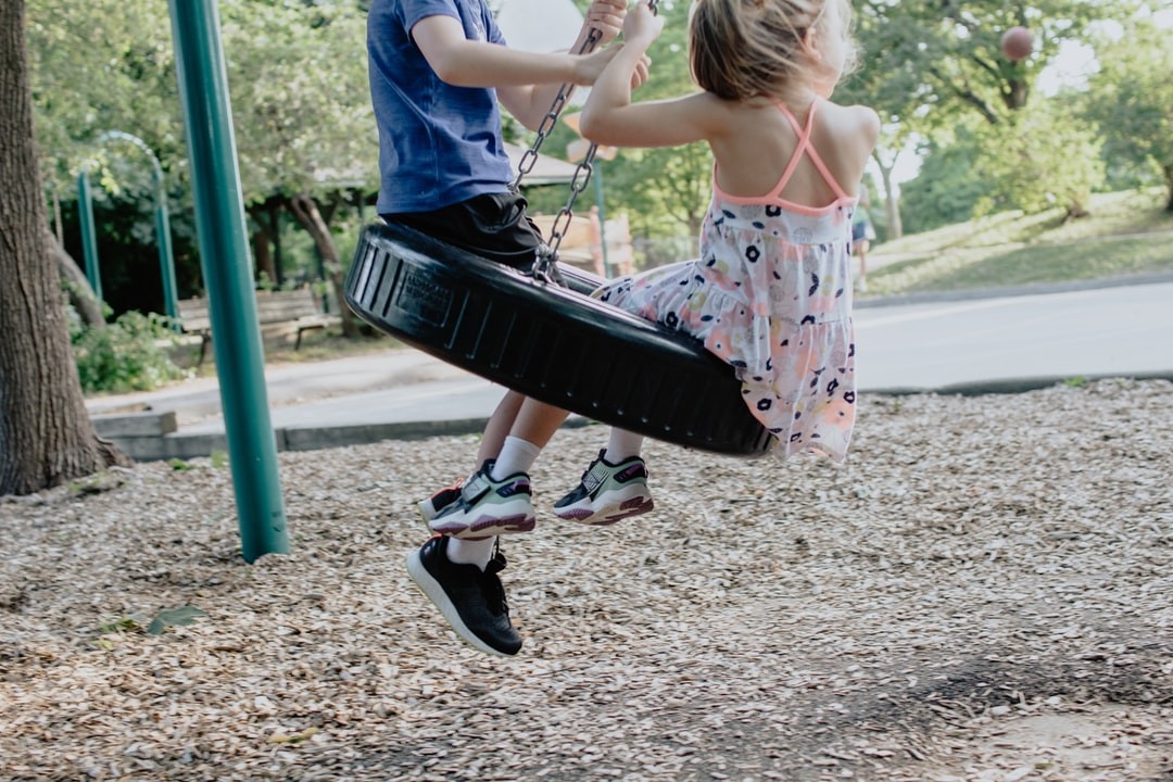 Kids swinging on a tire swing at a playground