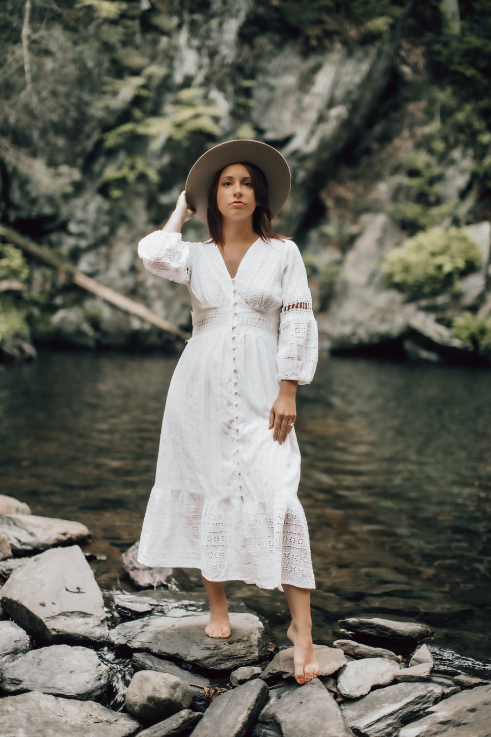 woman in white lace dress standing on rocky shore during daytime