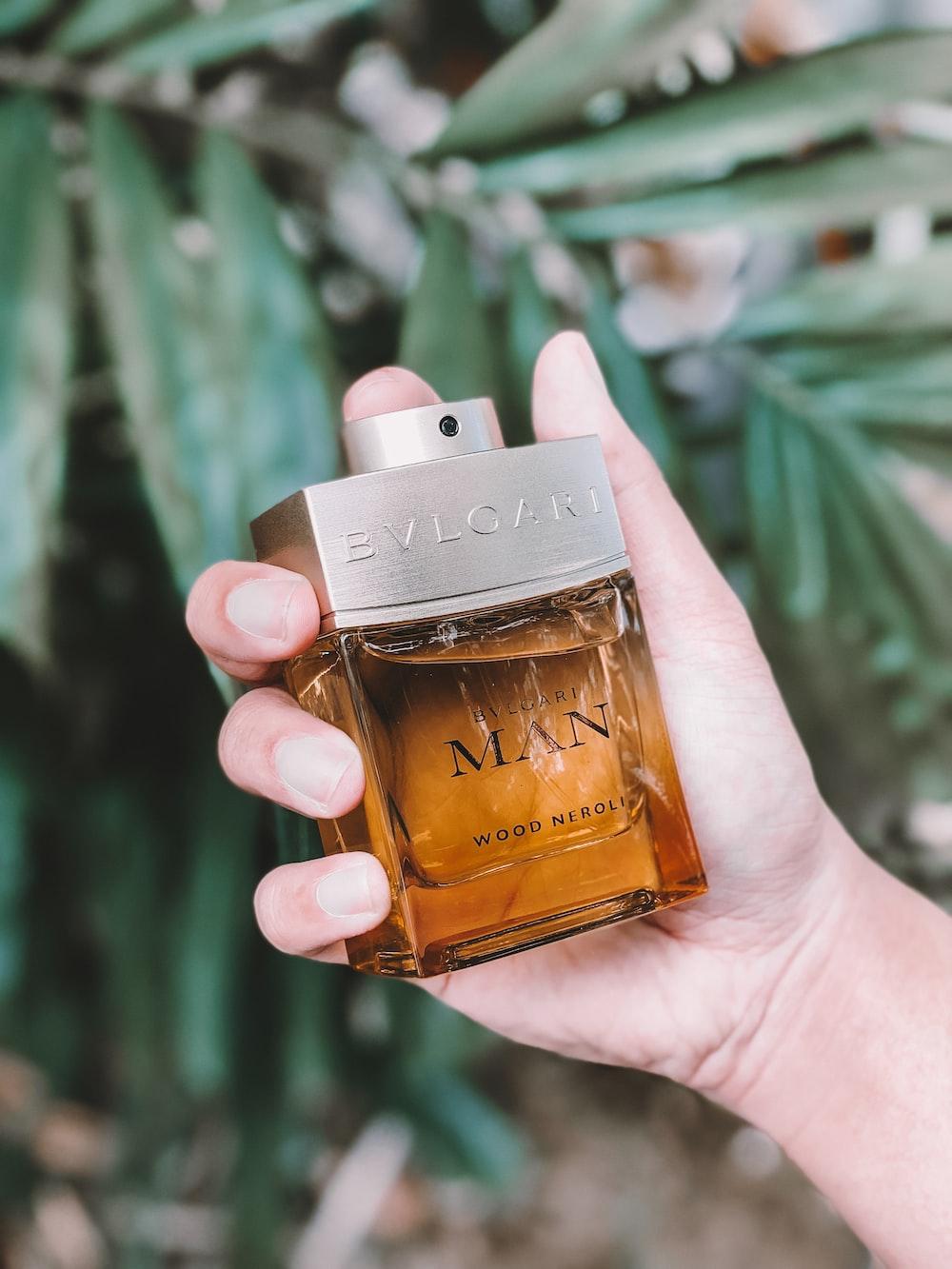 person holding calvin klein perfume bottle