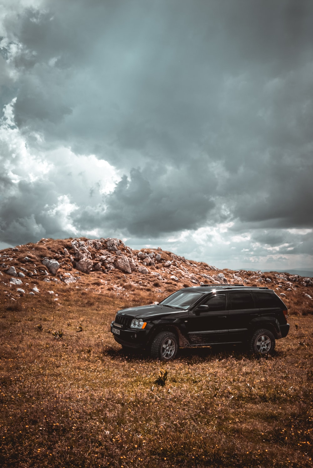 black suv on brown field under white clouds during daytime