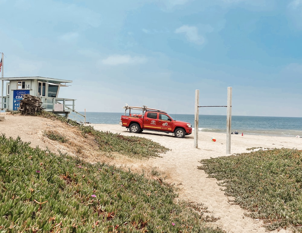red suv on beach shore during daytime