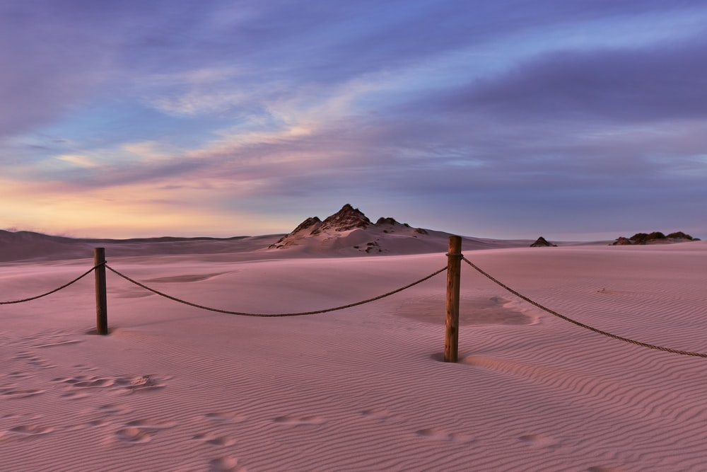 brown wooden post on brown sand during sunset