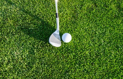 white golf club on green grass field golf teams background