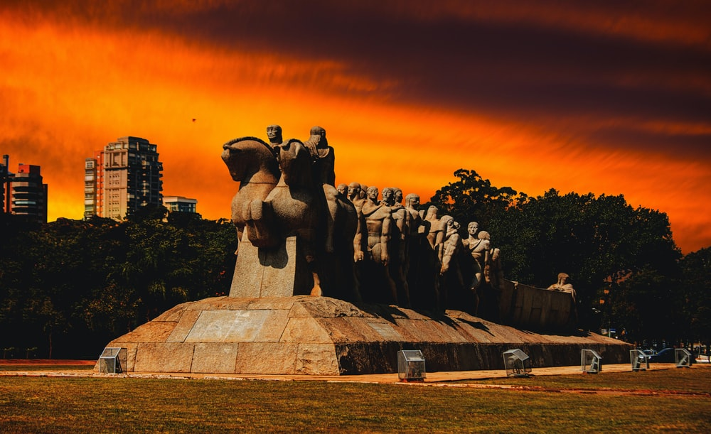 statue of people on green grass field during sunset