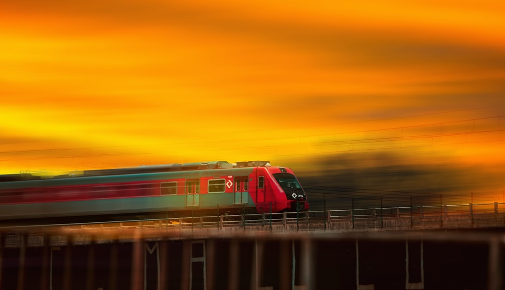 red and white train on rail during sunset