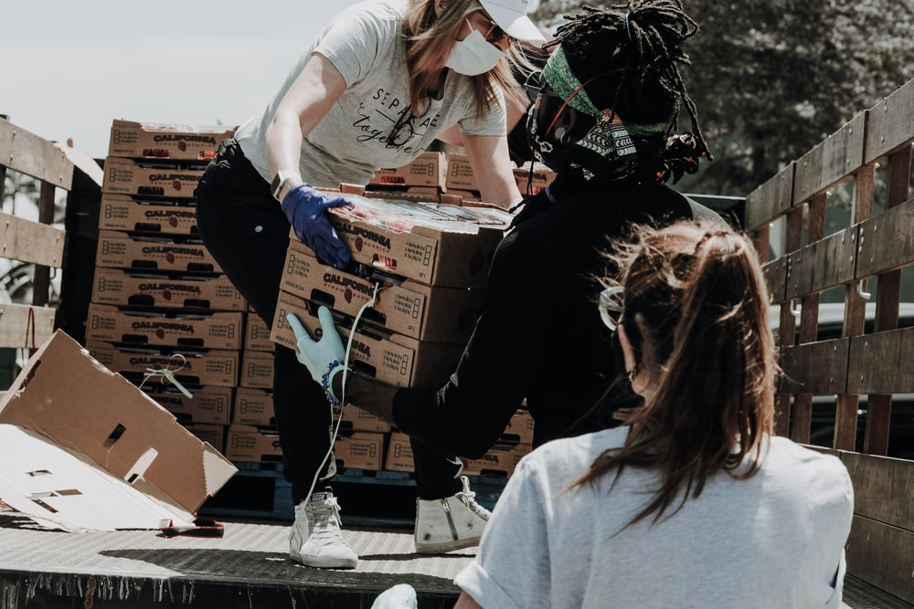 three volunteers wearing facemasks unloading boxes from a truck