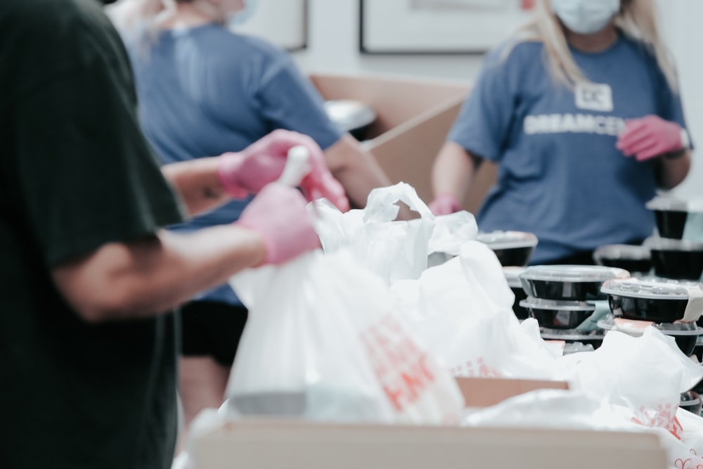 person in blue crew neck t-shirt holding white plastic bag