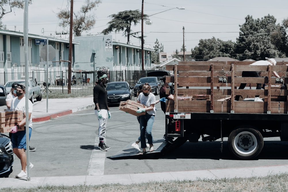 man in black jacket and blue denim jeans standing beside brown wooden box trailer during daytime