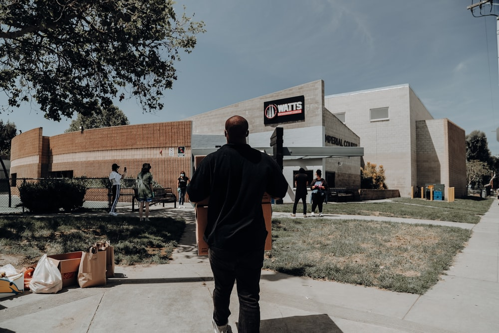 man in black hoodie standing near brown concrete building during daytime