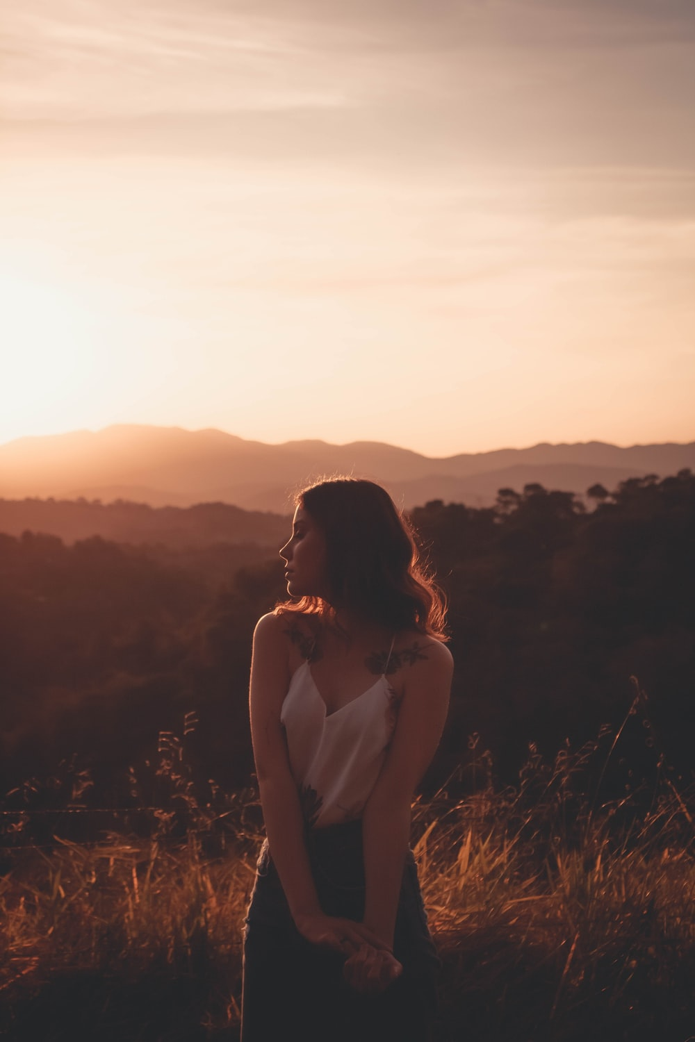 woman in white tank top sitting on brown grass during sunset