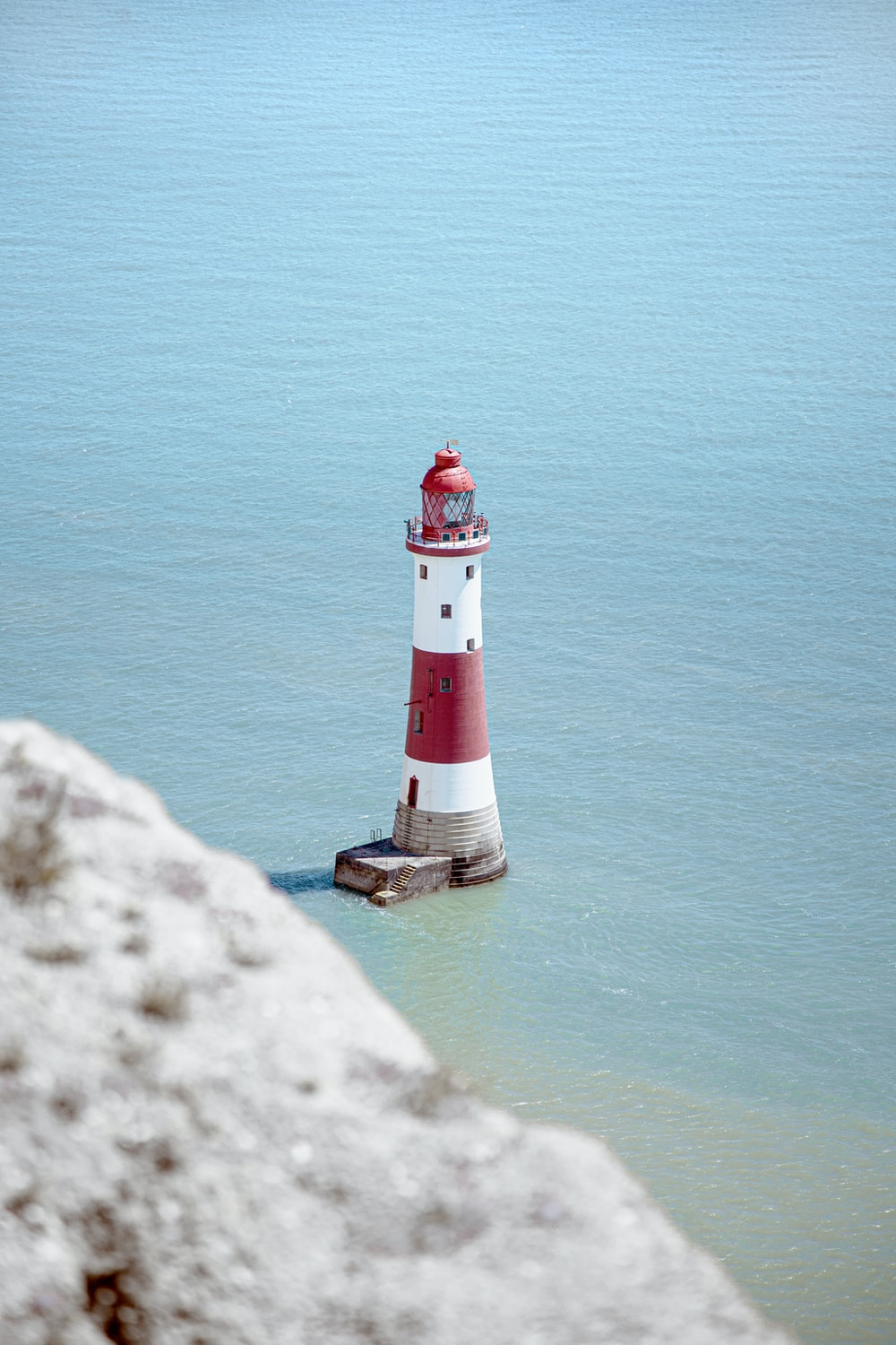 white and red lighthouse on rock formation beside body of water during daytime