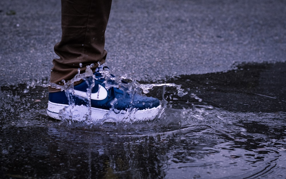person in blue and white nike sneakers standing on water