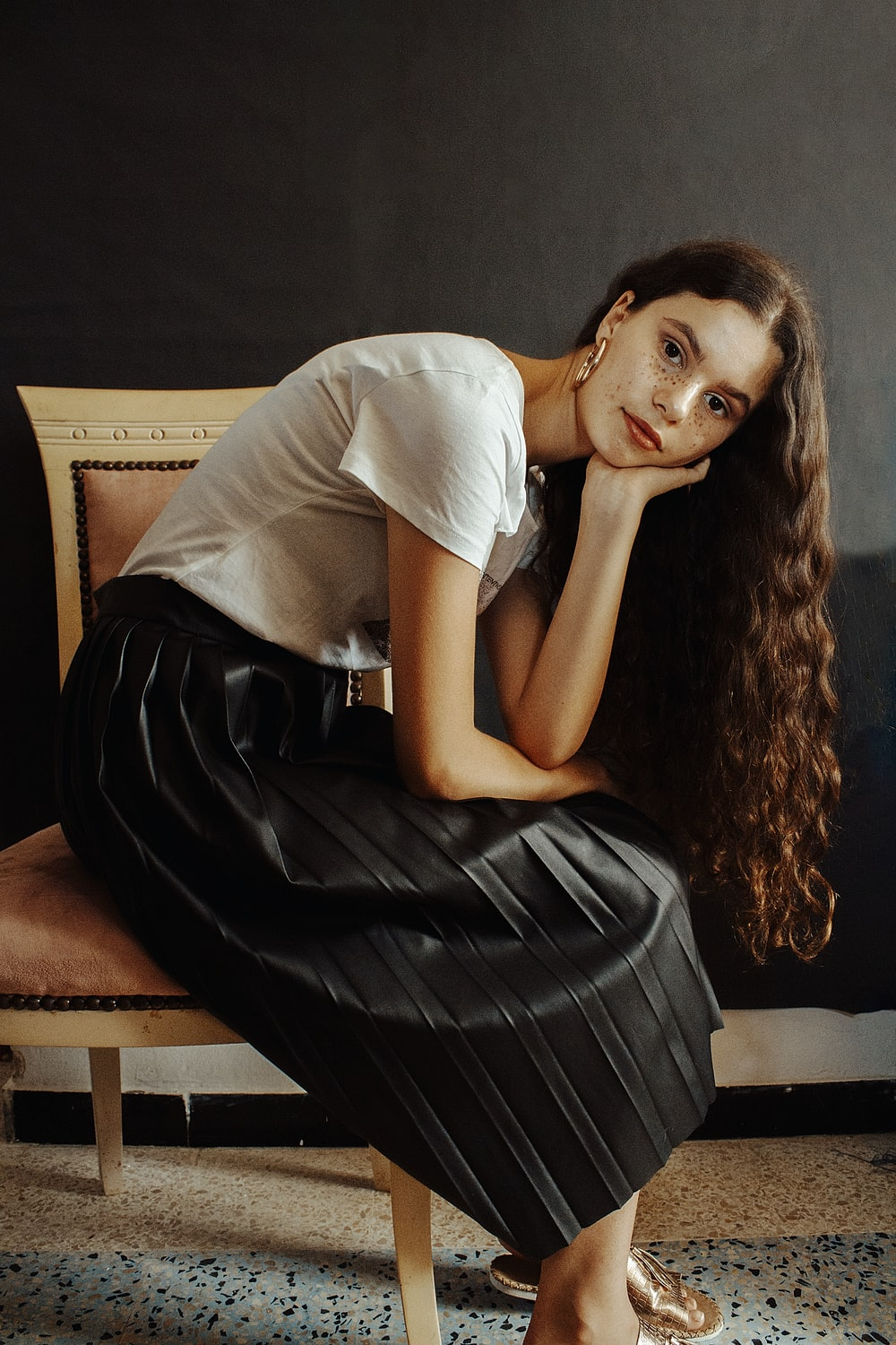 woman in white shirt and black skirt sitting on brown sofa
