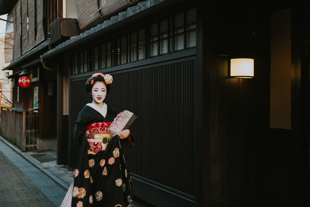 woman in black red and white floral kimono standing near black wooden door