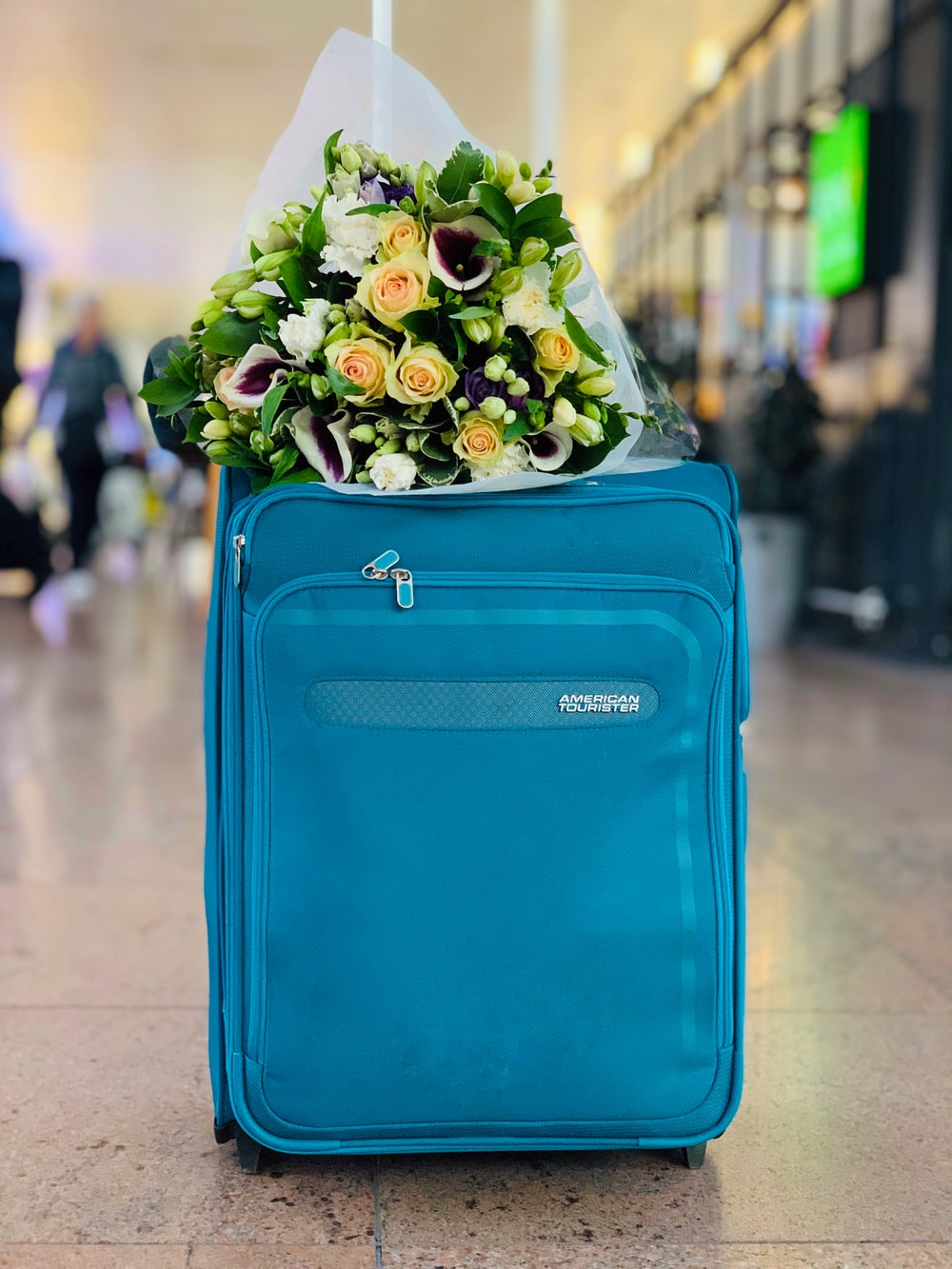 bouquet of flowers on blue luggage
