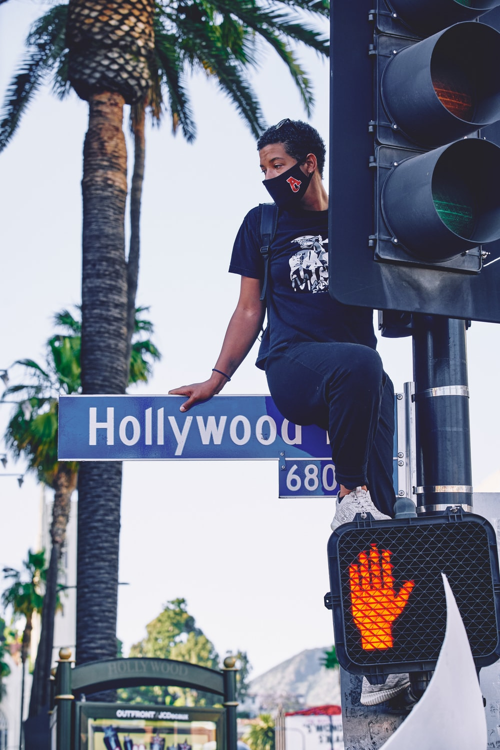 man in black t-shirt and black pants standing on black and white street light during