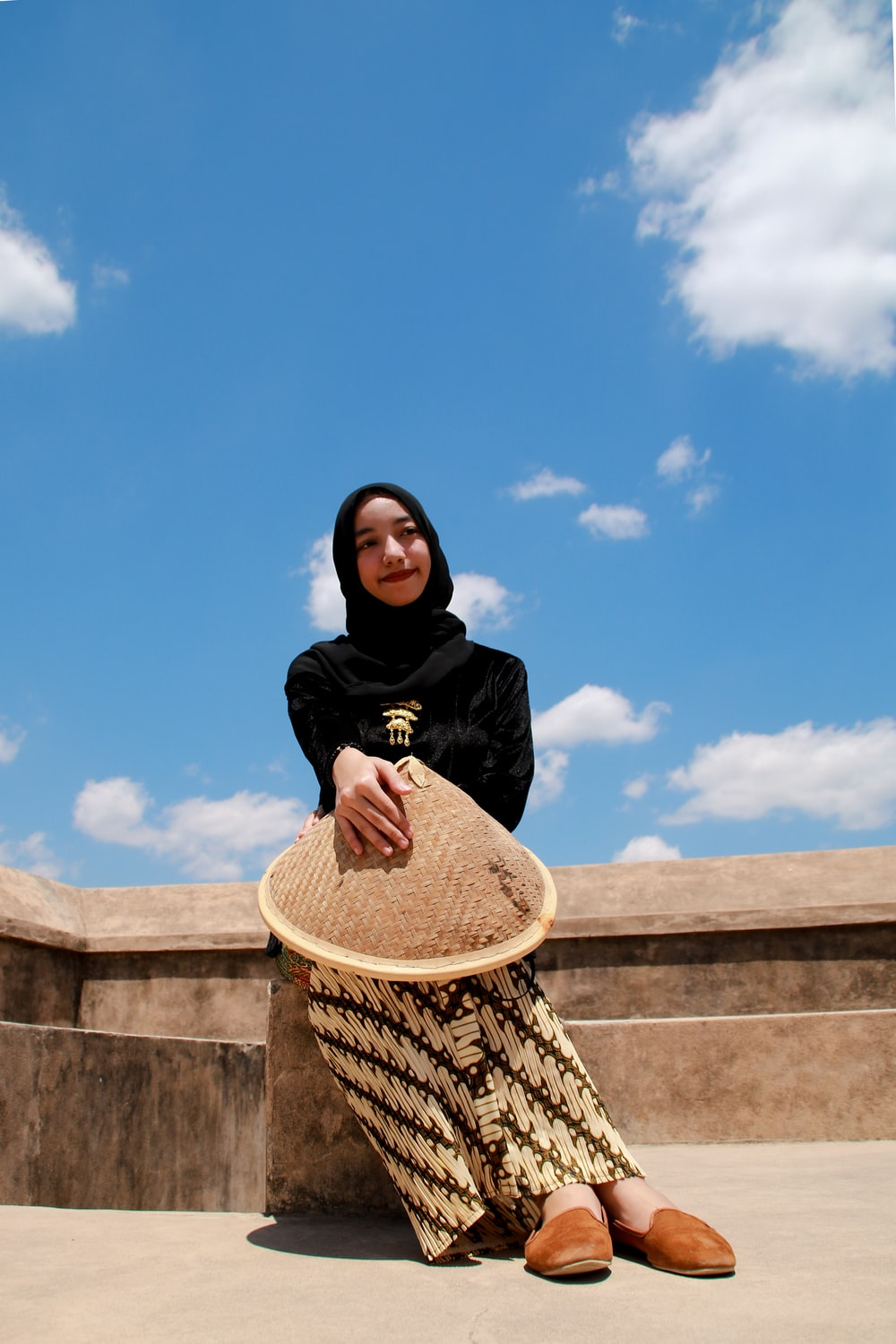 woman in black hijab and black long sleeve shirt sitting on brown concrete wall during daytime