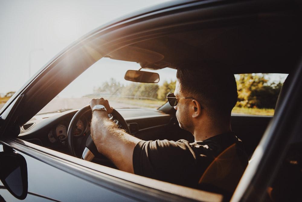 man in black jacket driving car during daytime